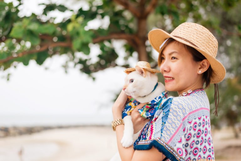 Asian woman carrying a cat in her hands